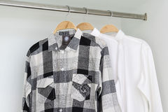 Row of shirts hanging in white wardrobe Royalty Free Stock Photos