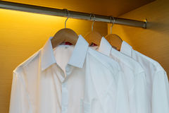 Row of shirts hanging in wooden wardrobe Royalty Free Stock Photography