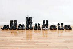 Row of shoes and boots on a wooden floor