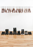 Row of shoes and empty hangers Royalty Free Stock Images