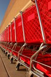 Row of shopping carts. A long row of red shopping carts Royalty Free Stock Photography