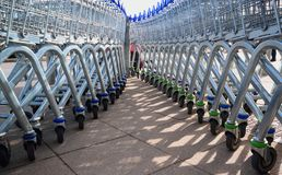 Row of shopping trolleys. Large group of shopping trolleys on wheels Stock Image