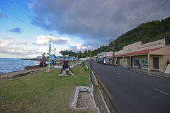 Row of shops, main road Beach Street & local Fijian sitting on public bench at Levuka, Ovalau island, Fiji. This image is taken close to evening sunset with Stock Photo