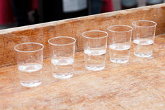 Row of shot glasses with vodka on wooden board Stock Image