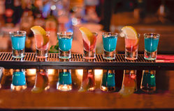 Row of shots on the bar. Tequila and blue curacao Royalty Free Stock Photography