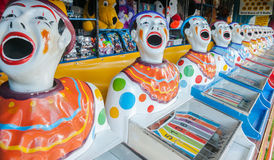 A row of sideshow carnival game clowns with mouths open diminish. Ing into distance Stock Image