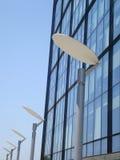 Row of silver metal lamps along glass building facade Stock Photo