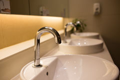 Row of sinks. A row of sinks and taps in a public toilet (washroom stock photography