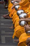 Row of sitting monks receiving alms stock photo