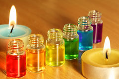 Row of six bottles with aroma oils. Row of six bottles with colored aroma oils and two candles on table Stock Photo