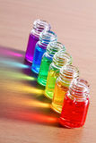 Row of six bottles of colored aromatic oils Royalty Free Stock Photos