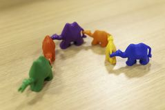 A row of six toy camels of different colors, holding each others tails. Diversity concept. Unique, but still united. royalty free stock photo