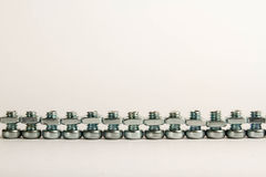Row of small steel nuts and bolts Stock Photo