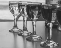 Row of small wine glasses with different wine black and white. Glasses of wine monochrome. Wine set elegant. stock images