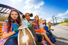 Row of smiling girls sitting on wooden bench Stock Images