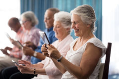 Row of smiling senior people sitting on chairs using digital tablets. At retirement home royalty free stock image