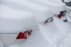 Row of snow-covered cars. A line of parked cars covered in snow Stock Image