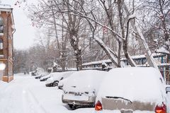 Row snow-covered cars and road in the courtyard in winter cloudy. Row parked snow-covered cars and  road in the courtyard during snowfall in winter cloudy Royalty Free Stock Image