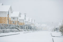 Row of the snowbound houses, homes with the sidewalk on empty st Royalty Free Stock Photos