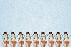 Row of Snowmen. Isolated against blue background Stock Photos