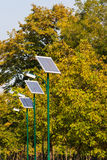 Row of solar powered street illuminators in the park with trees. Row of solar powered street illuminators in the park towards right with trees in background stock photos