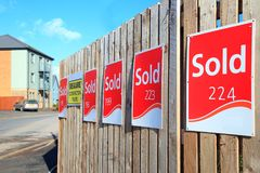 Row of sold signs. On the wooden fence at construction site stock photography