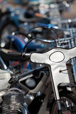 Row of speedway motorbikes outside in the sun. Row of shiny speedway motorcycles lined up outside on a sunny day Royalty Free Stock Photos