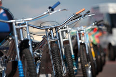 Row of speedway motorbikes outside in the sun. Row of shiny speedway motorcycles lined up outside on a sunny day Royalty Free Stock Images