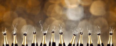 Splashing Champagne bottles with blurred lights in the background. A row of splashing champagne bottles with blurred lights in the background stock photo
