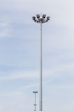 Row of sportlights tower in stadium with blue sky in background. Stock Images