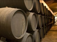 Row of stacked wooden wine barrels for sherry aging. Row of stacked oak casks or barrels along wall of winery for aging sherry or port Stock Photography