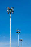 Row of stadium flood light towers on blue sky. Stock Images