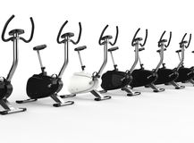 Row Of Stationary Bikes - one white Royalty Free Stock Photo