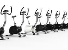 Row Of Stationary Bikes - one white Royalty Free Stock Photo