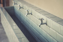 Row of steel taps into a large bathroom Royalty Free Stock Images