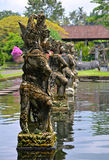 Row of stone sculptures at Tirtagangga Water Palace Bali Stock Photo