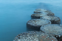 Row of stones stepping on the sea Stock Photos