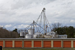 Row of storage units with agricultrual feed storage bins in the background. Royalty Free Stock Images