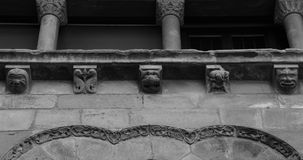 A row of strambotic characters on the facade. Shot in black and white, detail on the sculpture on the facade of this historic building representing some Stock Image