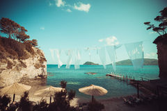 Row of Straw umbrellas and lounges at beach Zakynthos Stock Photos