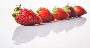 Row Of Strawberries Fruits VIII. Row of strawberry fruits over white background Royalty Free Stock Image