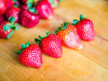 Row of strawberries on a wooden board. Row of fresh strawberries on a wooden board Royalty Free Stock Photo