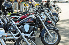 Row of street road motorbikes on bikie run. A line of hot shiny metal road motorcycles parked on the side of the busy town street, while the owner riders of the Stock Photos
