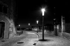 Row of streetlights in a curved and cobbled Street Stock Images