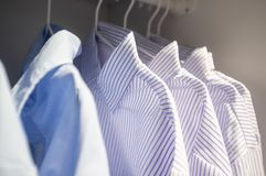 Row of striped business shirts on hangers. Row of striped business shirts on hangers in a wardrobe Stock Photo