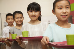 Row of students standing in line in school cafeteria Royalty Free Stock Image