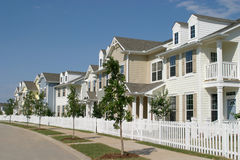 Row Of Suburban Townhouses. Long row of suburban townhouses with a white picket fence in front Stock Photo