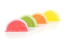 Sugar coated fruit jelly sweets. A row of sugar coated fruit jelly sweets on a white background Stock Photos