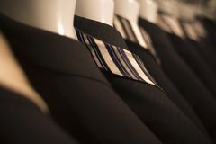Row Of Suits. A close up of a row of black, designer suits hanging in a men's fashion store Stock Image