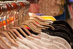 Row of summer shirts hanging on the counter, shopping. Fabric store, clothing store stock images